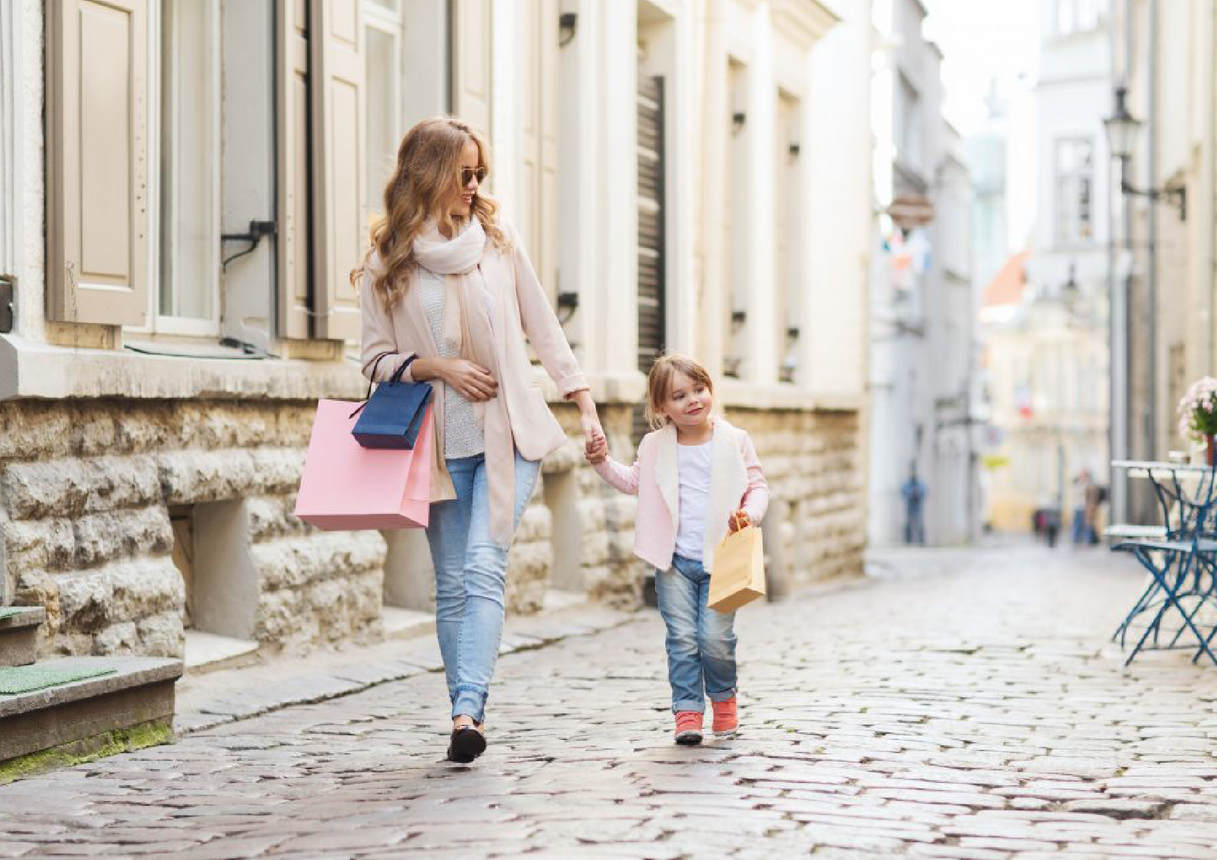 Mother & Daughter walking through the streets with shopping bags in hand