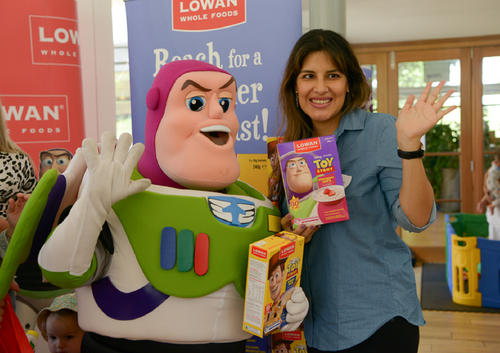 Influencer, Vanessa (Child Blogger) standing beside Buzz Lightyear showing Lowan's Whole Foods Toy Story range